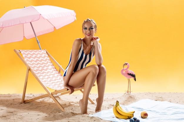 Concetto di estate modello sorridente in costume da bagno sulla sedia di spiaggia rosa