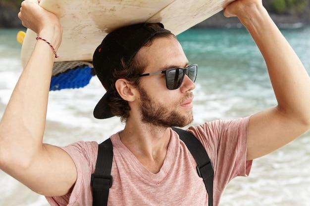 Concetto di estate, vacanze, tempo libero e stile di vita attivo. snapback d'uso ed occhiali da sole del giovane turista alla moda che stanno sulla riva di mare e che esaminano distanza