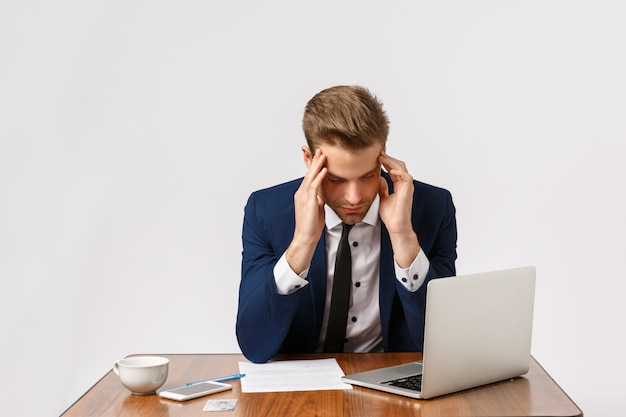 Concetto di fallimento, affaticamento e depressione. l'uomo che ha una brutta giornata, sentendosi deluso, perdendo un caso importante in tribunale, seduto a un tavolo da ufficio con laptop e documenti, toccando le tempie, ha mal di testa