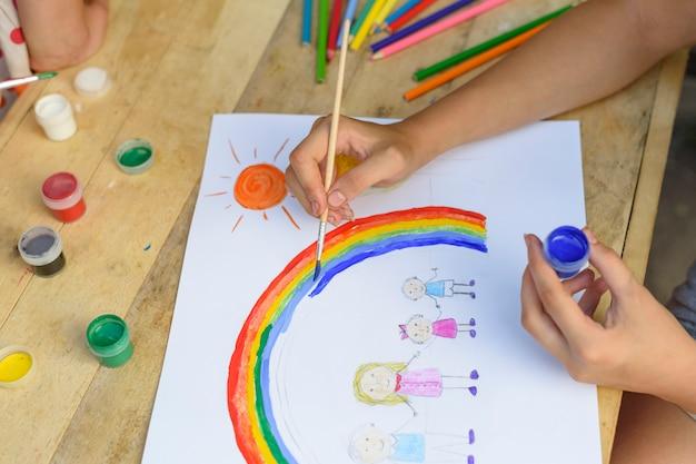 Concetto di famiglia felice. il bambino disegna su un foglio di carta: padre, madre, ragazzo e ragazza si tengono per mano