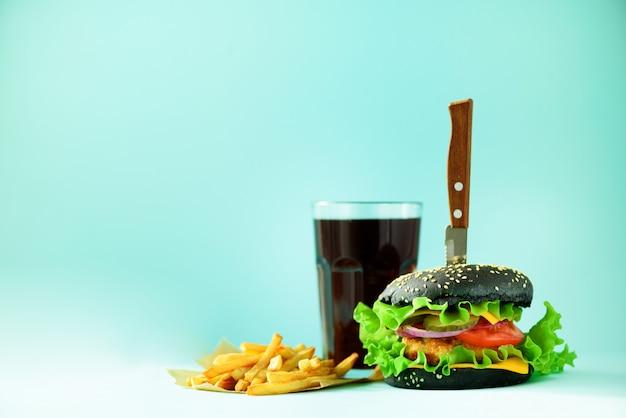 Concetto di fast food. hamburger fatti in casa succosi su sfondo blu. portare via il pasto telaio dieta malsana con spazio di copia