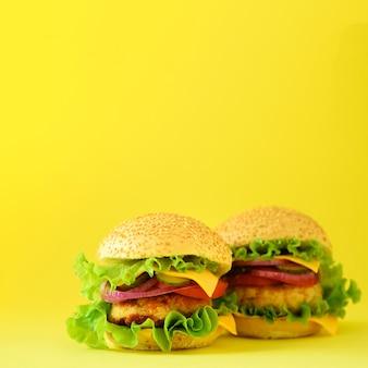 Concetto di fast food. raccolto quadrato. hamburger fatti in casa succosi su sfondo giallo. portare via il pasto cornice di dieta malsana