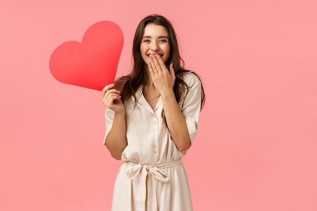 Concetto di felicità, relazione e romanticismo. seducente donna abbastanza femminile con i capelli ricci scuri, indossa un abito, ridendo la bocca della copertina come una risatina, con in mano un simpatico cuore rosso in cartone, parete rosa