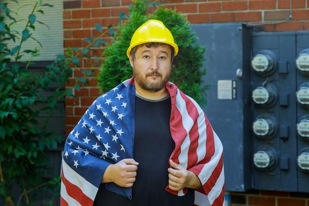 Concetto di festa del lavoro per il lavoratore in un casco giallo con una bandiera americana