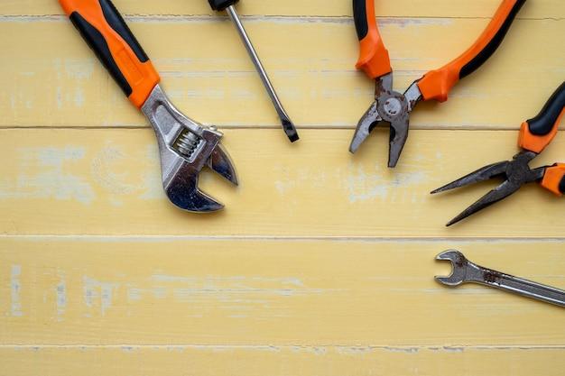 Concetto di festa del lavoro. strumenti di costruzione su superficie di legno gialla.
