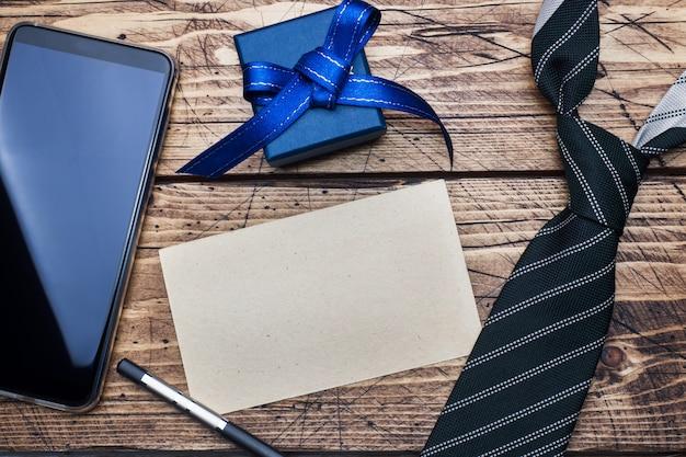 Concetto di festa del papà. cravatta a righe, scatola regalo e telefono e spazio per il testo sul tavolo di legno.