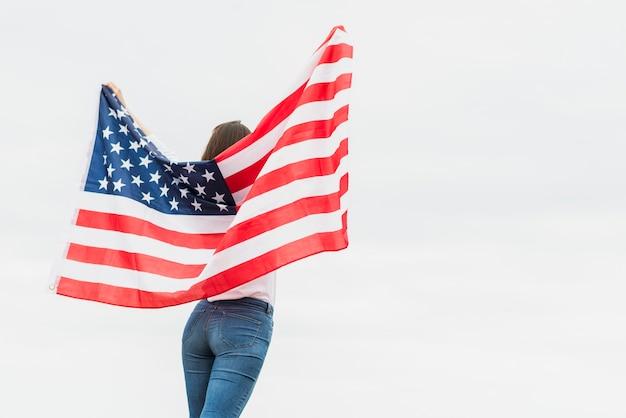 Concetto di festa dell'indipendenza con la bandiera della tenuta della donna sul fondo del cielo