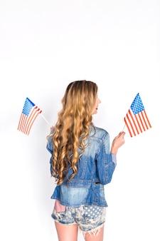 Concetto di festa dell'indipendenza degli stati uniti con il backview della donna con due bandiere