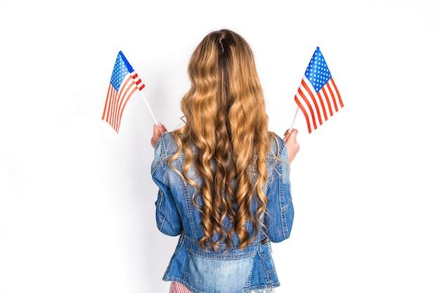 Concetto di festa dell'indipendenza degli stati uniti con il backview della donna con le bandiere