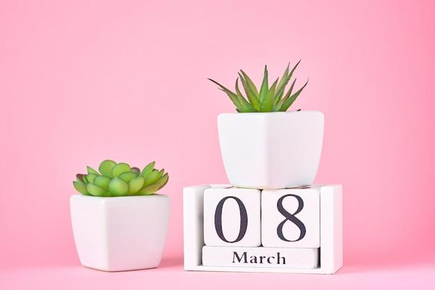 Concetto di festa della donna. blocchetto di calendario di legno con la data l'8 marzo e pianta sul rosa con lo spazio della copia