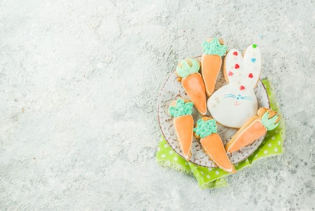 Concetto di festa di pasqua, biscotti dolci nella forma di carote, coniglietto di pasqua, con le uova variopinte, vista superiore, spazio di pietra grigio della copia del fondo