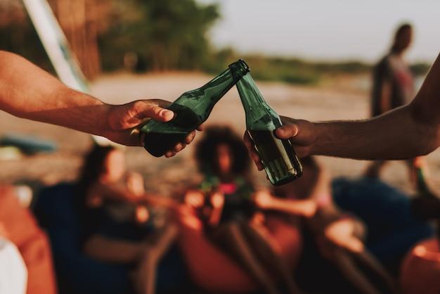 Concetto di festa in spiaggia. giovane azienda beve birra.