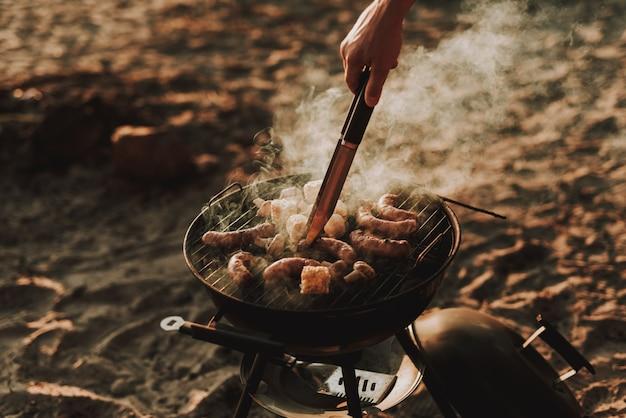 Concetto di festa in spiaggia. man grills barbecue sausages.