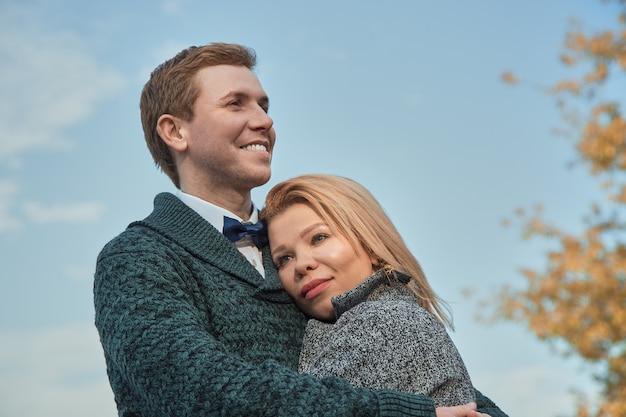 Concetto di feste, di amore, di viaggio, di turismo, di relazione e di datazione - coppia romantica nel parco di autunno