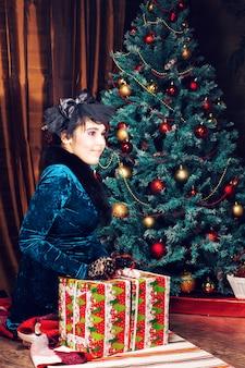 Concetto di feste, di celebrazione e della gente - donna sorridente in vestito che tiene il contenitore di regalo rosso sopra le luci dell'albero di natale