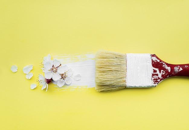 Concetto di fiore di primavera. pennello con il fiore del fiore dell'albicocca su fondo giallo.