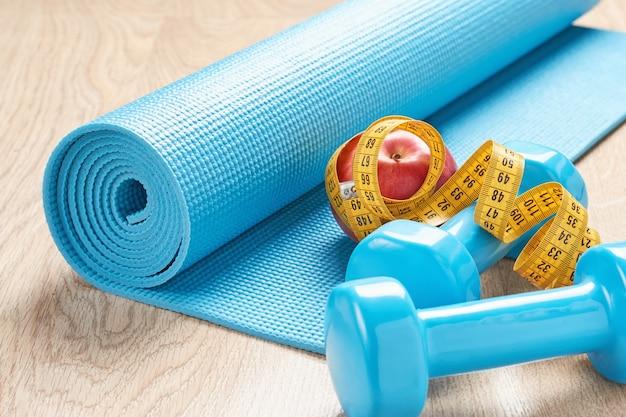 Concetto di fitness con manubri blu, tappetino fitness e un nastro di misurazione