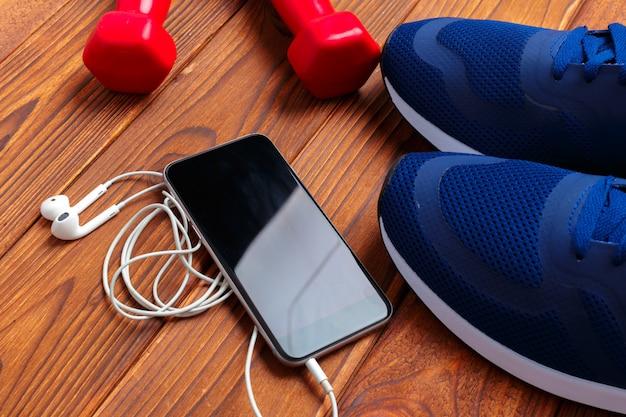 Concetto di fitness con scarpe da ginnastica, manubri