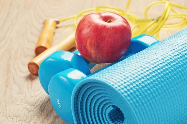 Concetto di fitness con un manubri blu e tappetino yoga