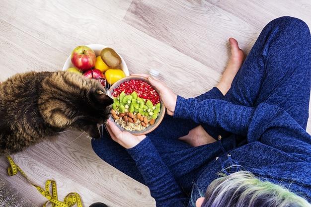 Concetto di fitness e stile di vita sano. la femmina sta riposando e sta mangiando una farina d'avena sana dopo un allenamento. vista dall'alto.