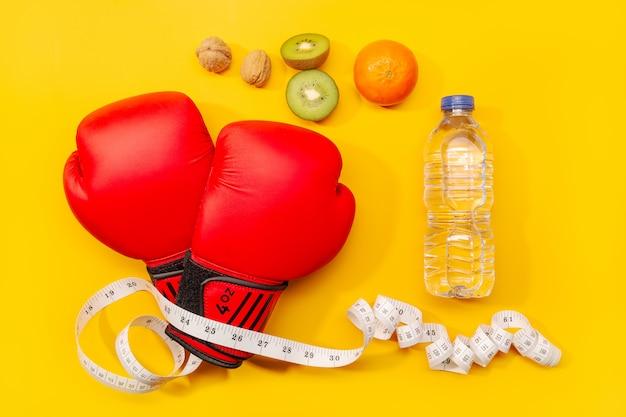 Concetto di fitness, perdita di peso o esercizio fisico. guantoni da pugile, alimento sano e nastro di misura isolati