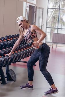 Concetto di fitness, sport, allenamento e stile di vita. gruppo di donne felici con manubri che flettono i muscoli in palestra