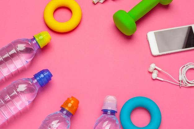 Concetto di forma fisica con bottiglia d'acqua, telefono cellulare con auricolari