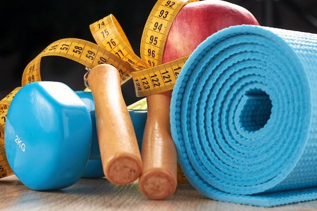 Concetto di forma fisica con manubri blu, tappetino fitness e corda per saltare su uno sfondo scuro