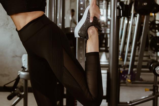 Concetto di forma fisica, di sport, di addestramento, della palestra e di stile di vita - vicino su della gente con l'istruttore che si esercita e che allunga la gamba in palestra.
