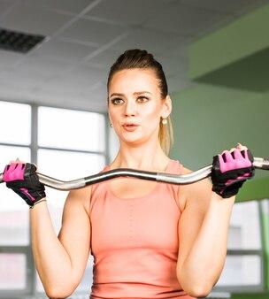 Concetto di forma fisica, di sport, di addestramento e di stile di vita - donna felice con il bilanciere che flette i muscoli in palestra