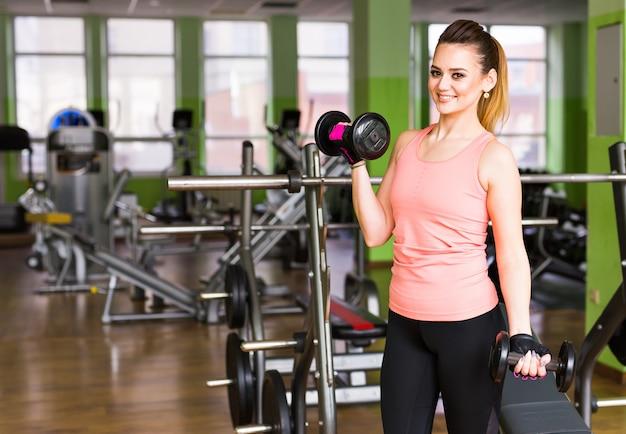 Concetto di forma fisica, di sport, di addestramento e di stile di vita - donna felice con le teste di legno che flette i muscoli in palestra
