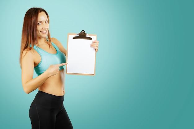 Concetto di forma fisica, di sport, di esercitazione e di dieta - istruttore personale sorridente della giovane donna con la lavagna per appunti