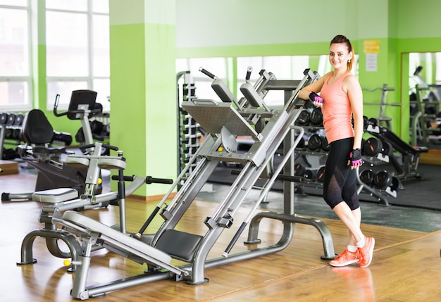 Concetto di forma fisica, sport, allenamento e stile di vita - donna felice in palestra