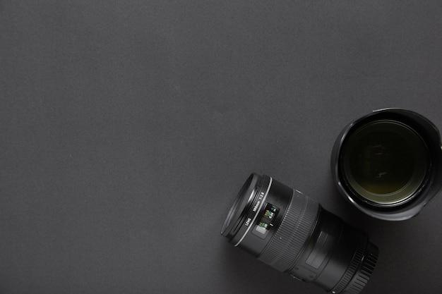 Concetto di fotografia con gli obiettivi su fondo nero e spazio della copia