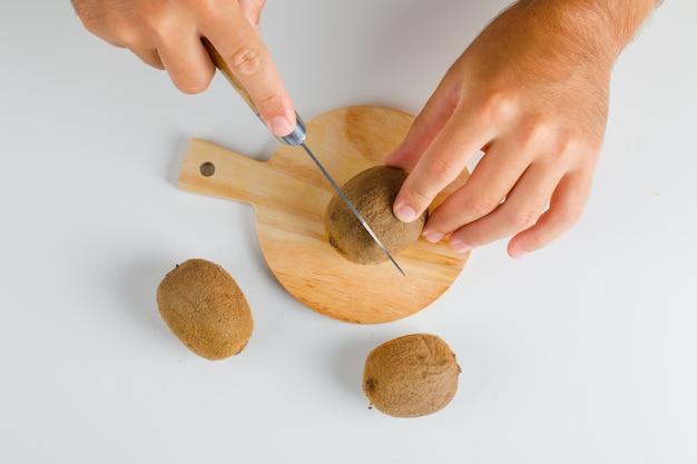 Concetto di frutta piatto disteso. mani che tagliano kiwi su tavola di legno.