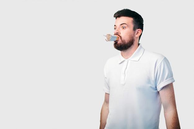 Concetto di fumo. il ragazzo dai capelli scuri con la barba tiene molte sigarette in bocca.