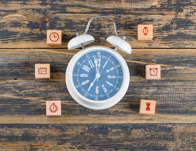 Concetto di gestione del tempo con blocchi di legno con icone, grande orologio sul tavolo di legno piatto laici.