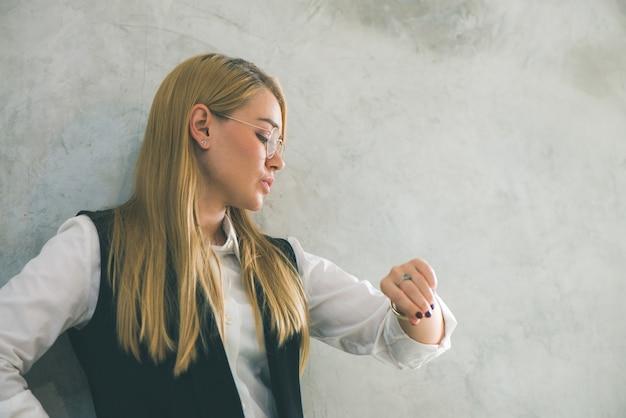 Concetto di gestione del tempo e del business. giovane imprenditrice guardando orologio da polso. il tempo è denaro