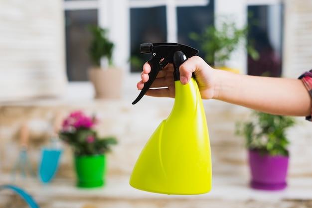 Concetto di giardinaggio con la mano che tiene flacone spray