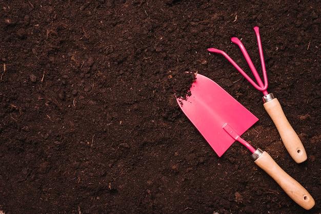 Concetto di giardinaggio con pala e rastrello sul terreno