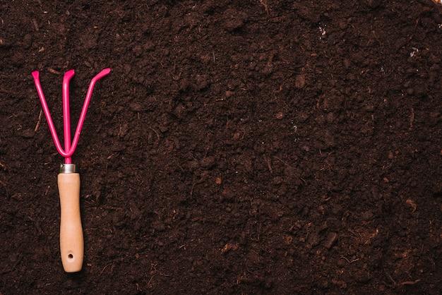 Concetto di giardinaggio con rastrello sul terreno