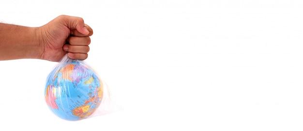 Concetto di giornata mondiale dell'ambiente. la mano dell'uomo tiene la terra in un sacchetto di plastica su bianco