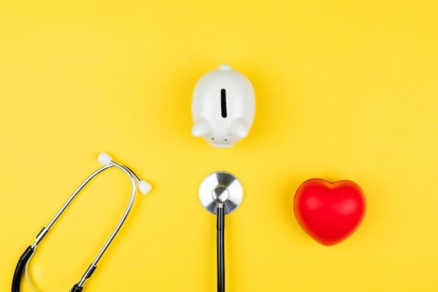 Concetto di giornata mondiale della salute assicurazione sanitaria con cuore rosso, cassa di risparmio e stetoscopio