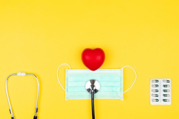 Concetto di giornata mondiale della salute assicurazione sanitaria con cuore rosso, stetoscopio, maschera e medicina
