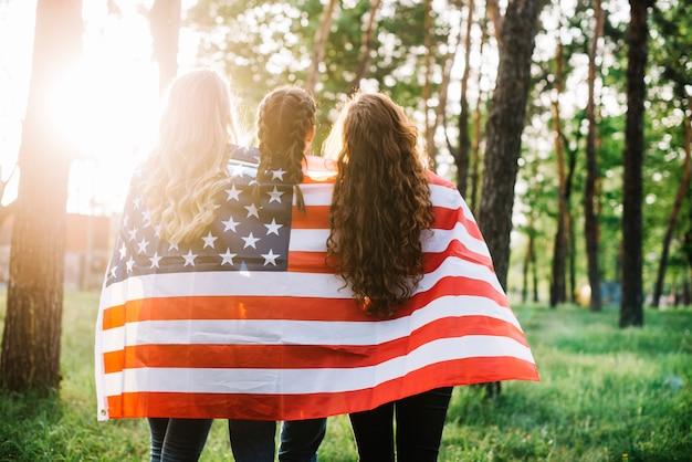 Concetto di giorno di indipendenza con backview di ragazze nella foresta
