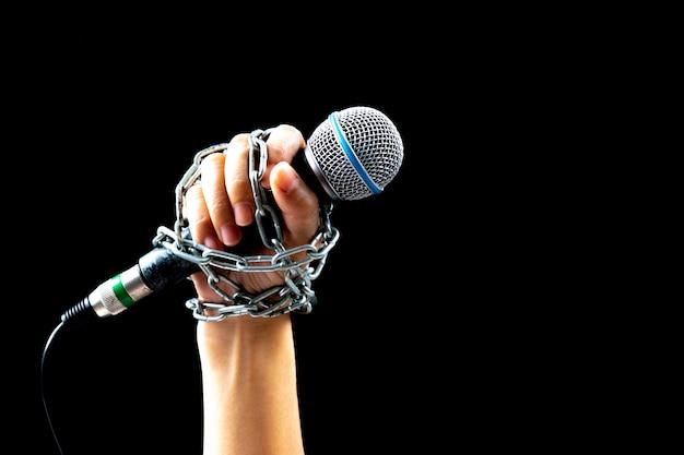 Concetto di giorno di libertà di stampa mondiale. mano di donna con microfono legato con una catena