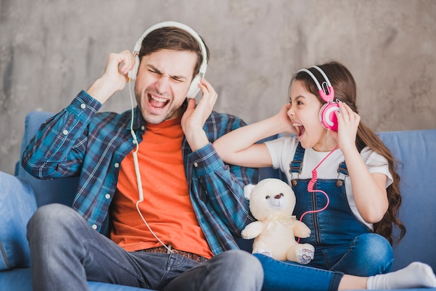 Concetto di giorno di padri con padre e figlia ascoltando musica