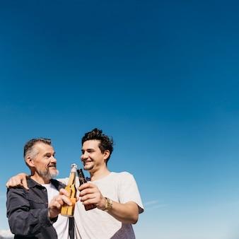 Concetto di giorno di padri con padre e figlio che tostano con la birra davanti a sfondo del cielo