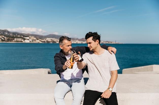 Concetto di giorno di padri con padre e figlio che tostano con la birra di fronte al mare