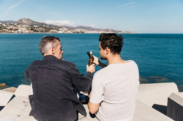 Concetto di giorno di padri con padre e figlio che tostano con la birra di fronte oceano